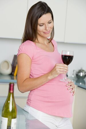 Pregnant woman in kitchen with glass of red wine smiling Фото со стока