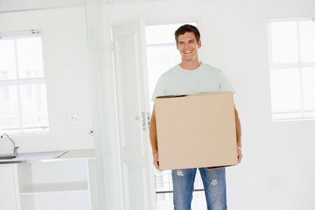 first time buyer: Man with box moving into new home smiling