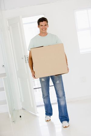 property ladder: Man with box moving into new home smiling