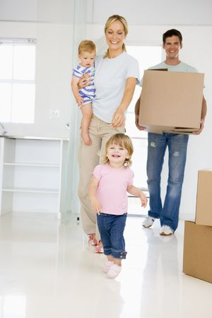 family moving house: Family with box moving into new home smiling