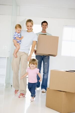 new home family: Family with box moving into new home smiling