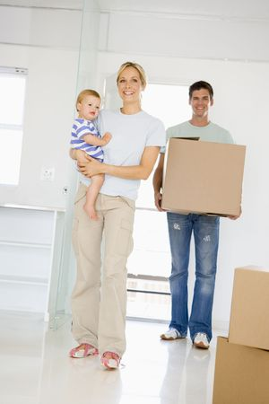 first time buyer: Family with box moving into new home smiling