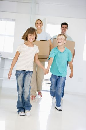 Family with boxes moving into new home smiling Stock Photo - 3485875