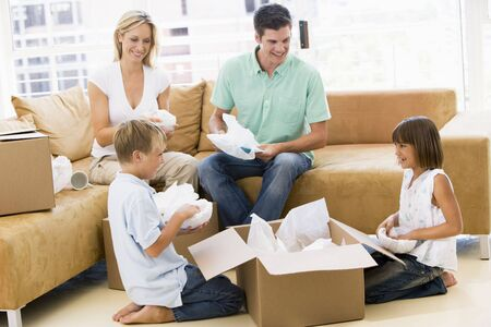Family unpacking boxes in new home smiling photo