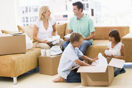 Family unpacking boxes in new home smiling Stock Photo - 3487039