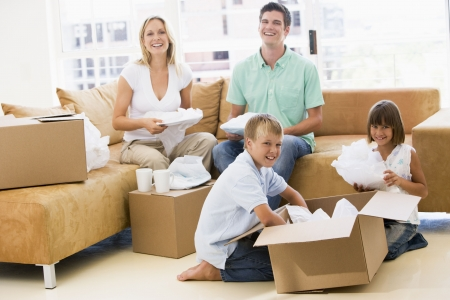 Family unpacking boxes in new home smiling Stock Photo - 3486970