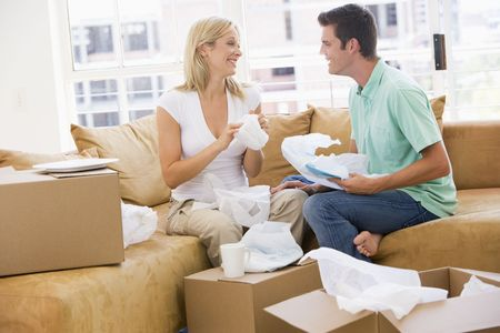 property ladder: Couple unpacking boxes in new home smiling