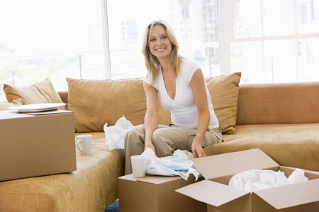 unfurnished: Woman unpacking boxes in new home smiling Stock Photo