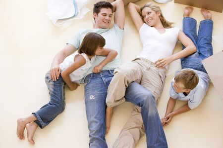 Family lying on floor by open boxes in new home smiling photo