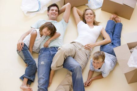lying on the floor: Family lying on floor by open boxes in new home smiling