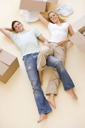 Couple lying on floor by open boxes in new home smiling Stock Photo - 3486231