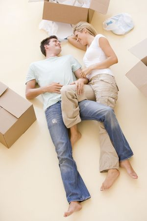 overhead view: Couple lying on floor by open boxes in new home smiling Stock Photo