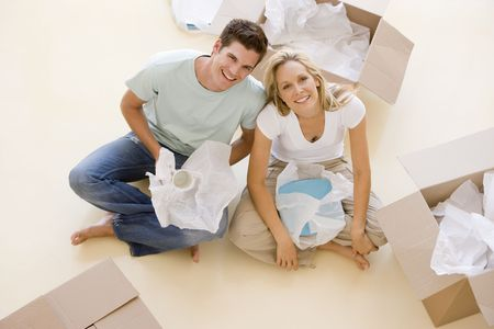 Couple sitting on floor by open boxes in new home smiling Stock Photo - 3486078