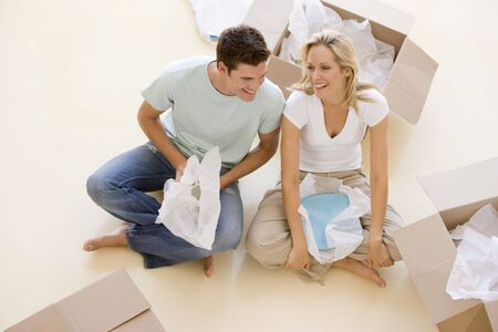 Couple sitting on floor by open boxes in new home smiling Stock Photo - 3485857