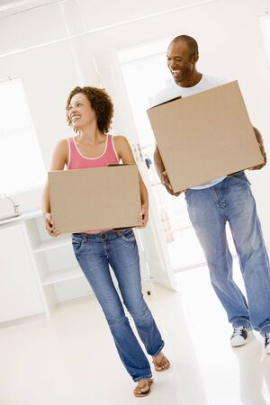 Couple with boxes moving into new home smiling photo