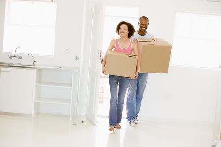 first time buyer: Couple with boxes moving into new home smiling