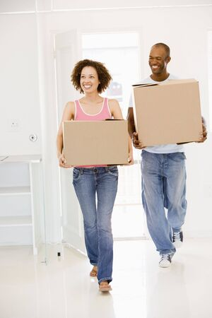 property ladder: Couple with boxes moving into new home smiling