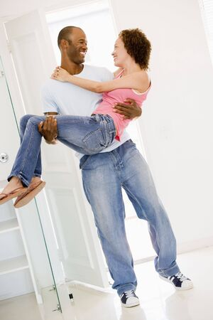 Husband holding wife in new home smiling Stock Photo - 3486748