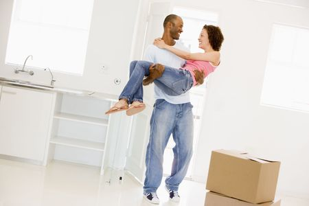 man carrying woman: Husband holding wife in new home smiling Stock Photo
