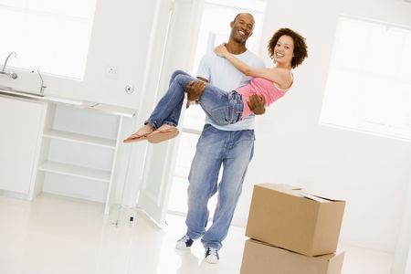 Husband holding wife in new home smiling Stock Photo