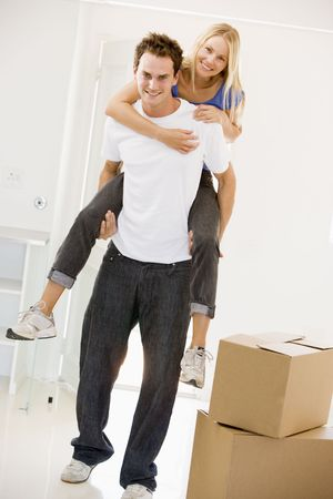 Husband giving wife piggyback in new home smiling photo