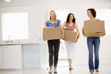 Three girl friends moving into new home smiling photo