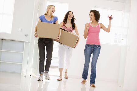 first time buyer: Three girl friends moving into new home smiling Stock Photo