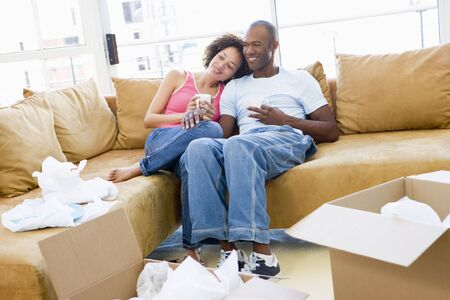 unpacking: Couple relaxing with coffee by boxes in new home smiling Stock Photo