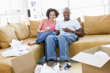Couple relaxing with coffee by boxes in new home smiling photo