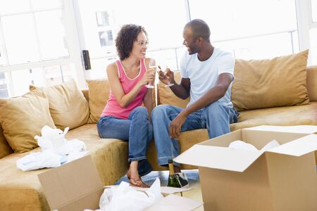proposing a toast: Couple toasting champagne by boxes in new home smiling