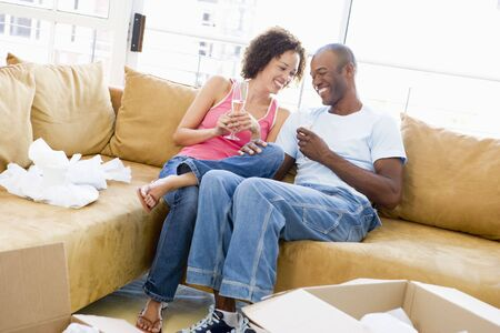 Couple relaxing with champagne by boxes in new home smiling Stock Photo - 3487220