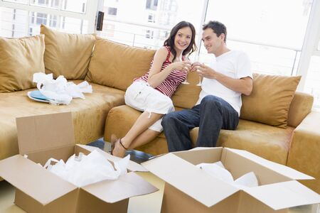 first time buyer: Couple relaxing with champagne by boxes in new home smiling Stock Photo