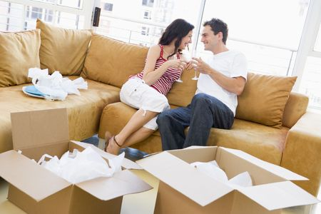 unpacking: Couple relaxing with champagne by boxes in new home smiling Stock Photo