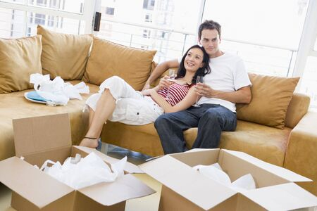 Couple relaxing with champagne by boxes in new home smiling Stock Photo - 3486983
