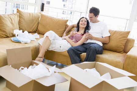 alcohol cardboard: Couple relaxing with champagne by boxes in new home smiling Stock Photo