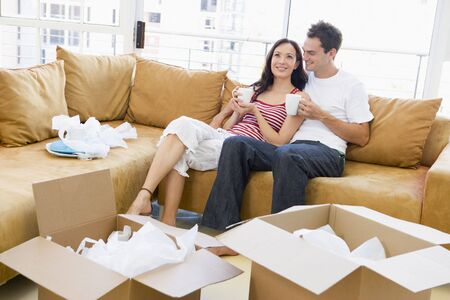 first time buyer: Couple relaxing with coffee by boxes in new home smiling Stock Photo