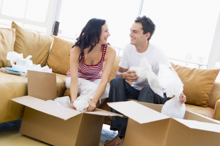 first time buyer: Couple unpacking boxes in new home smiling