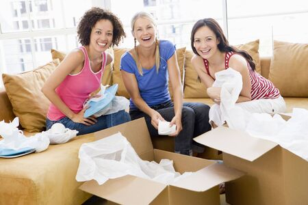 Three girl friends unpacking boxes in new home smiling photo