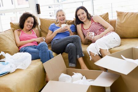 Three girl friends relaxing with coffee by boxes in new home smiling photo