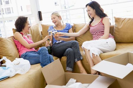 proposing a toast: Three girl friends toasting champagne by boxes in new home smiling