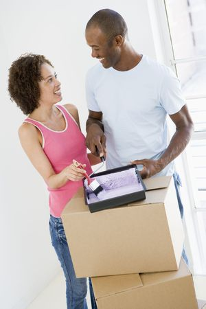 first time buyer: Couple with roller and paint in new home smiling