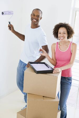Couple with roller and paint in new home smiling photo