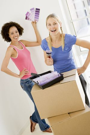 property ladder: Two women with paint swatches in new home smiling