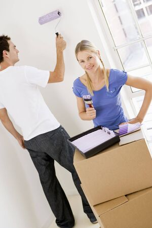 first time buyer: Couple painting room in new home smiling Stock Photo