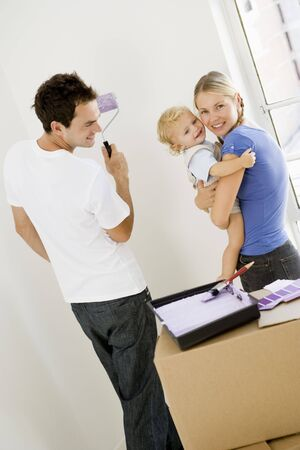 Family painting room in new home smiling Stock Photo - 3486255