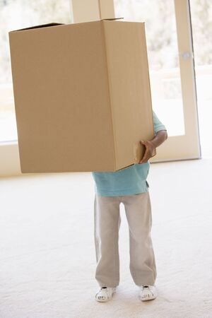 first time buyer: Young boy holding box in new home