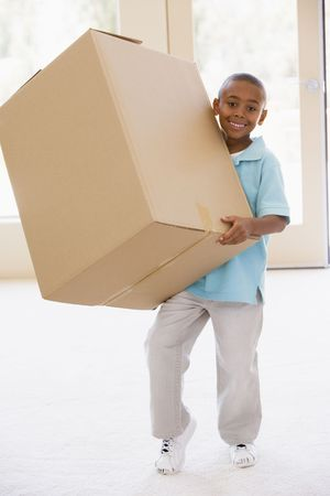 Young boy holding box in new home smiling photo