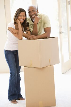 first time buyer: Couple with boxes in new home smiling