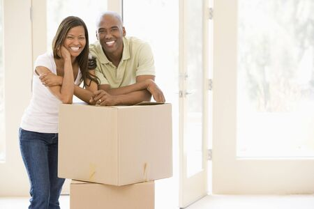 man carrying woman: Couple with boxes in new home smiling