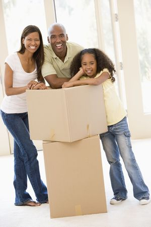 Family with boxes in new home smiling Stock Photo - 3487177
